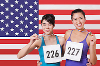 Portrait of smiling young medalists standing against American flag