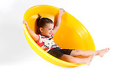 Indoor playground Young girl rolling in a half sphere  On white Background