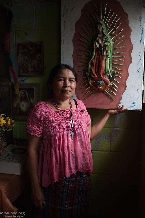 Paulina Chen Osorio, 44, survivor from Rio Negro, stands near a window inside a special room-turned-shrine in her home. She hopes the Forensic Anthropology Foundation of Guatemala (FAFG) identifies and returns her father Pedro Chen, and brothers Daniel (15), Carlos (7) and Francisco (6) who were either killed or abducted during the May 14, 1982, Los Encuentros Massacre and possibly exhumed in 2012 from grave XV at the UN's CREOMPAZ training center, formerly Coban's Military Zone 21. During the massacre, Guatemalan soldiers and civil patrolmen killed 79 community members from Rio Negro who were hiding here after the previous two massacres of February and March of the same year. Eyewitnesses assured that at least 15 other community members were abducted in a helicopter. As of May 2016, CREOMPAZ's grave XV has rendered positive DNA matches of the remains of two victims abducted in the helicopter on such day. Paulina is not sure if her father and siblings were killed in Los Encuentros or taken by Helicopter. Her mother Narcisa Osorio Lopez was killed along with 176 other women and children during the March 13, 1982, massacre at Pak'oxom peak near Rio Negro. Paulina lives in Pacux, the resettlement village outside Rabinal where the former Achi Mayan residents of Rio Negro were forcibly relocated after the massacres and destruction of their village and dozens more due to the flooding of the Chixoy river basin and construction of the Chixoy Hydro-electric project. Pacux, Rabinal, Baja Verapaz, Guatemala. May 20, 2016.