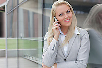 Portrait of young businesswoman communicating on cell phone while leaning on glass wall