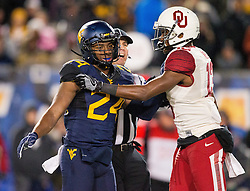 Nov 19, 2016; Morgantown, WV, USA; West Virginia Mountaineers cornerback Maurice Fleming (24) and Oklahoma Sooners wide receiver A.D. Miller (13) push each other after a play during the second quarter at Milan Puskar Stadium. Mandatory Credit: Ben Queen-USA TODAY Sports