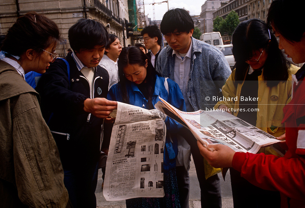 Members of Chinese exile community keep vigil and await more news outside their embassy a day after the Tiananmen Sq massacre. Catching up on the latest from home, the young Chinese activists read newspapers reporting of the massacre by the Chinese regime on protesting students in Beijing. The political crackdown that initiated on June 3–4 1989 became known as the Tiananmen Square Massacre as troops with assault rifles and tanks inflicted casualties on unarmed civilians trying to block the military's advance towards Tiananmen Square in the heart of Beijing, which student demonstrators had occupied for seven weeks.