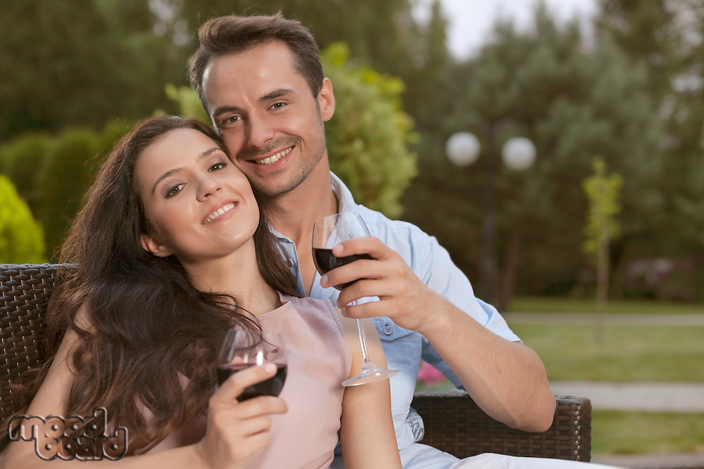 Portrait of happy young couple having red wine together in park