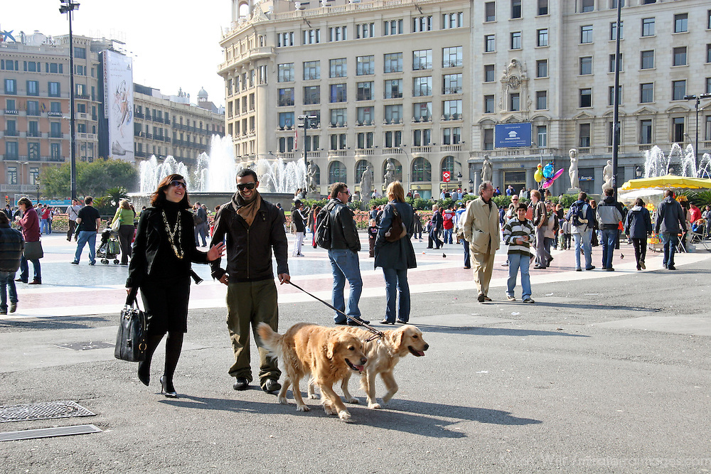 Europe, Spain, Barcelona. A couple walks dogs amongst shoppers in Barcelona.
