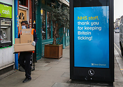 © Licensed to London News Pictures. 31/03/2020. London, UK. A delivery man with boxes walks past 'NHS Staff, thank you for keeping Britain ticking!' coronavirus public information poster in north London as lockdown continues. Photo credit: Dinendra Haria/LNP