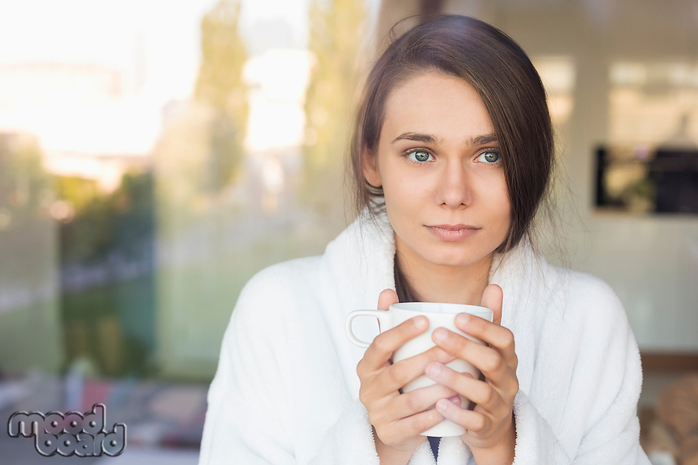 Sick young woman holding coffee mug at home