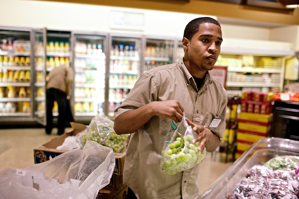 Elio Perdomo, restocks grapes in the produce section at a Safeway grocery store in Silver Sping, MD. Perdomo, a student at Montgomery College, tries to take classes in the morning and works up to 16 hours a week at the supermarket.