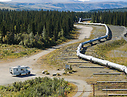 """The Trans Alaska Pipeline (or Alyeska Pipeline) crosses the Alaska Range and conveys crude oil 800 miles (1287 km) from Prudhoe Bay to Valdez, Alaska, USA. The 48-inch diameter (122 cm) pipeline is privately owned by the Alyeska Pipeline Service Company. The Trans Alaska Pipeline System (TAPS) includes """"The Pipeline"""", several hundred miles of feeder pipelines, 11 pump stations, and the Valdez Marine Terminal. Environmental, legal, and political debates followed the discovery of oil at Prudhoe Bay in 1968. After the 1973 oil crisis caused a sharp rise in oil prices in the United States and made exploration of the Prudhoe Bay oil field economically feasible, legislation removed legal challenges and the pipeline was built 1974-1977. Extreme cold, permafrost, and difficult terrain challenged builders. Tens of thousands of workers flocked to Alaska, causing a boomtown atmosphere in Valdez, Fairbanks, and Anchorage. Oil began flowing in 1977. The pipeline delivered the oil spilled by the huge 1989 Exxon Valdez oil tanker disaster, which caused environmental damage expected to last 20-30 years in Prince William Sound."""