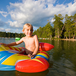 A boy on his floating toy at the beach at White Lake State Park in Tamworth, New Hampshire.