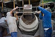 Men poring gravel into cement mixer making concrete, housing contruction Baños, Ecuador