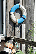 Lobster buoys and Cape Cod life ring on weathered wood on exterior of building