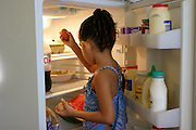 (MODEL RELEASED IMAGE). Sinead Brown grazes through her grandparent's nearly-empty refrigerator in the kitchen of their rented home in Riverview, Australia (near Brisbane). Every two weeks a new check appears and the family goes to the supermarket. (Supporting image from the project Hungry Planet: What the World Eats.)