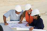 Architect and two construction workers looking at blueprints on construction site