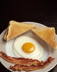 breakfast plate one fried egg sunny side up two slice bacon toast on plate Bon Appetit