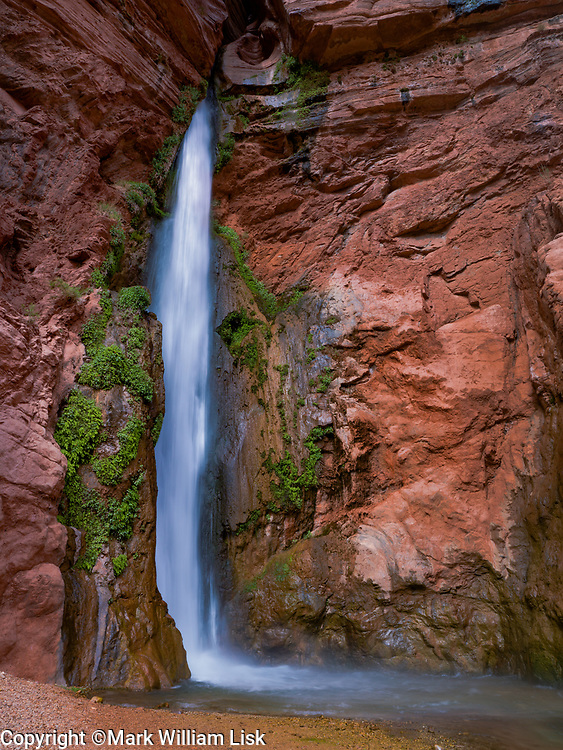 Deer Creek Falls pours from a slot high in the Canyon Wall to the Colorado River below.