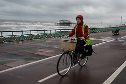 © Licensed to London News Pictures. 15/09/2015. Brighton, UK. A cyclist wrapped up on her bike riding to work along Brighton promenade as high winds and heavy rain batter Brighton seafront on  the south coast of England.  Photo credit: Ben Cawthra/LNP