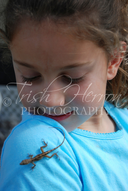 A young girl enjoys watching a lizard crawling on her shoulder.