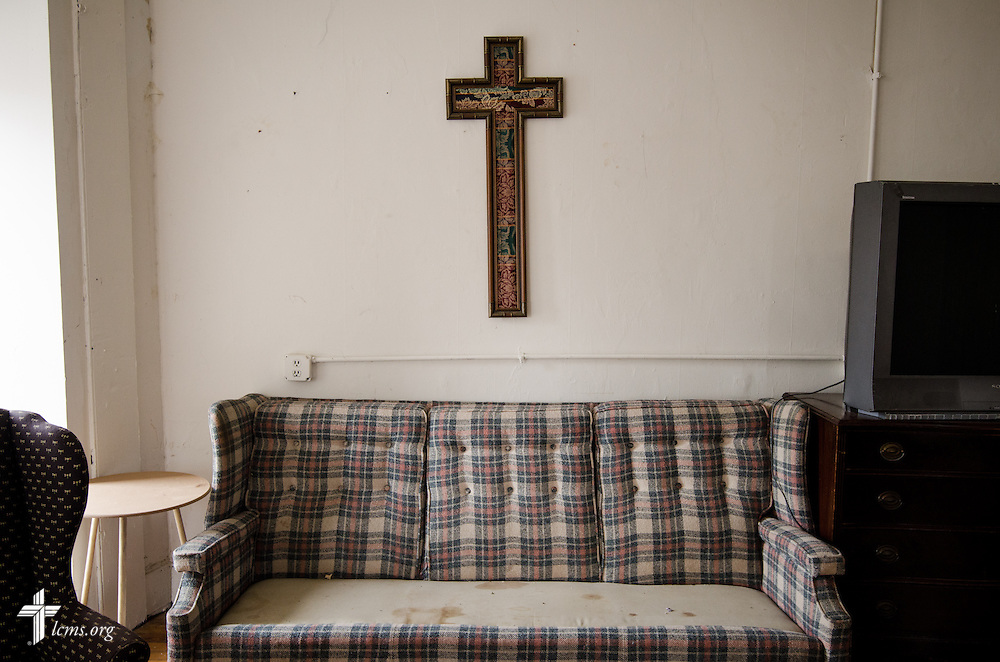 A cross hangs above a couch void at The Concordia House recovery center on Friday, March 28, 2014, in Baltimore, Md. LCMS Communications/Erik M. Lunsford