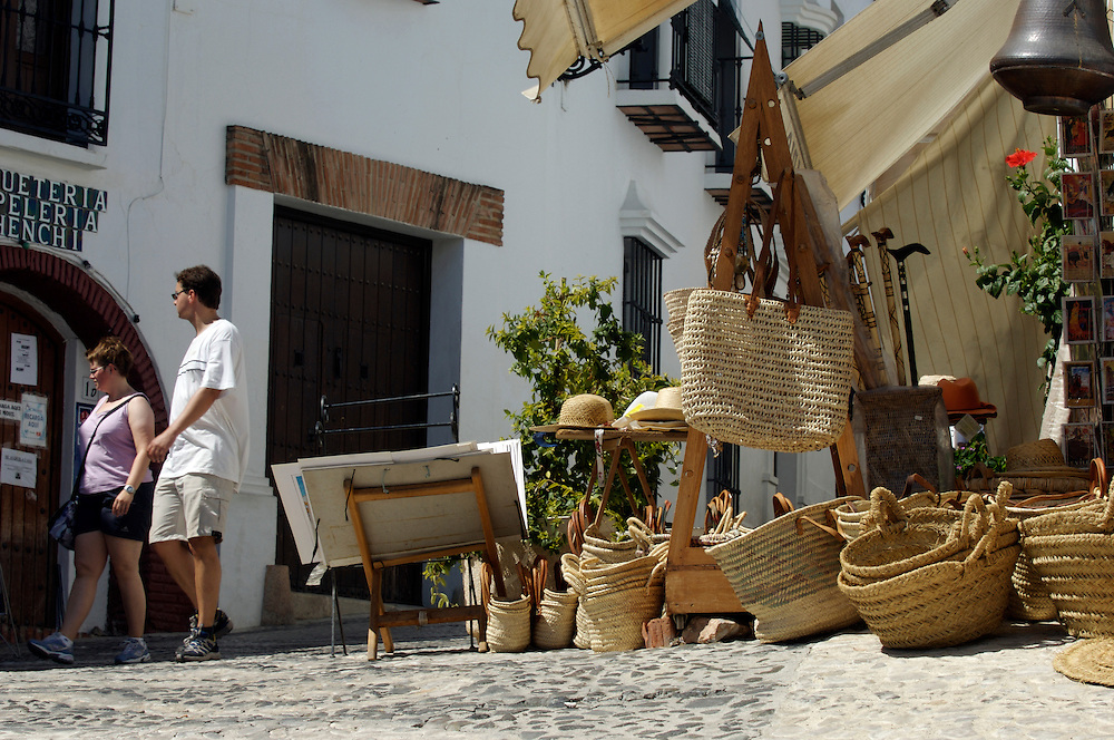 Tourist walk past a basket shop in Frigiliana, a white village on the Costa del Sol, Spain