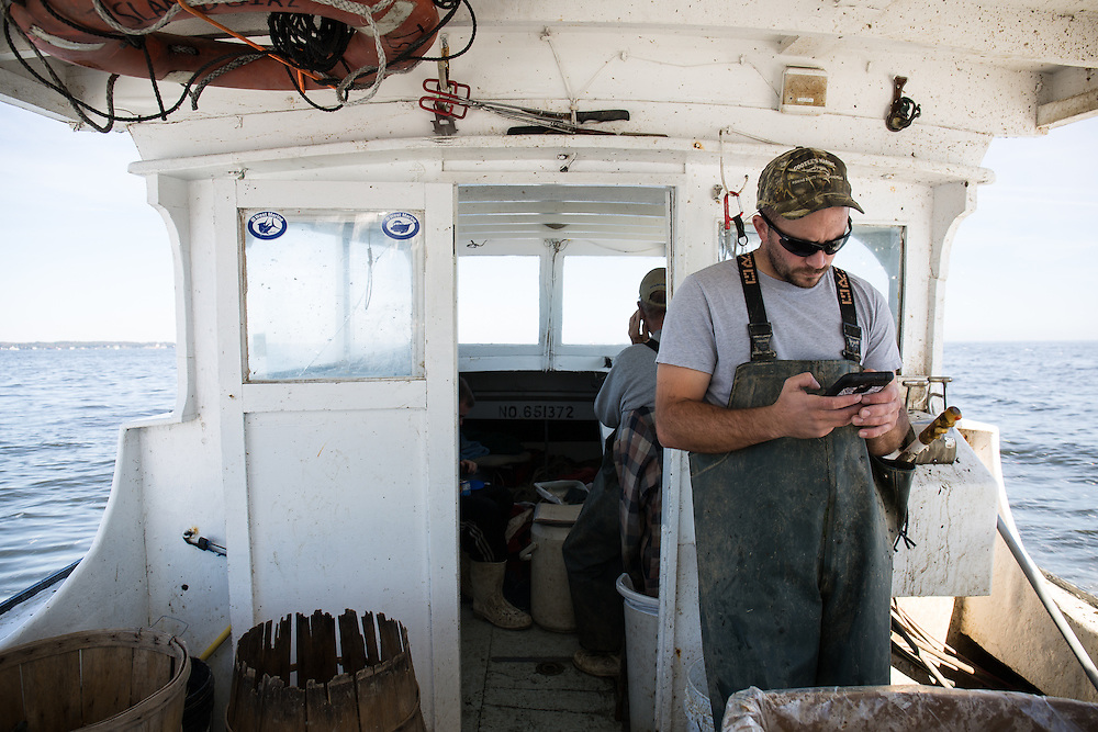 Captain Richard and Ryan Ribb check their messages during a short break while traveling between areas with crab traps.  | October 11, 2015