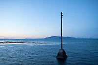 A pole in the sea by Grotta lighthouse at night