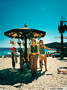 Two women standing next to a stall selling bikinis on the beach, Jockey Club, Salinas beach. Ibiza, 1998