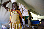 (MODEL RELEASED IMAGE). The Breidjing Refugee Camp, Eastern Chad on the Sudanese border shelters 30,000 people who have fled their homes in Darfur, Sudan. Food is distributed free of charge by the United Nations WFP (World Food Program). Here 12 year old Acha Aboubakar prepares to take her family's (her mother is a widow and she has 4 brothers and sisters) ration of grain ground into meal at a portable diesel powered mill operated by a local entrepreneur who is paid with a small percentage of the grain. (Supporting image from the project Hungry Planet: What the World Eats.)