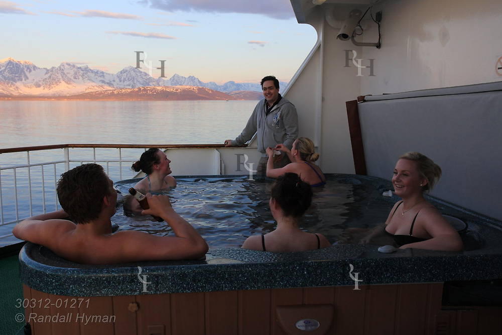 Staff aboard Hurtigruten coastal cruise ship enjoy time off in hot tub in late evening in mid May near Lyngen mountains, Norway.