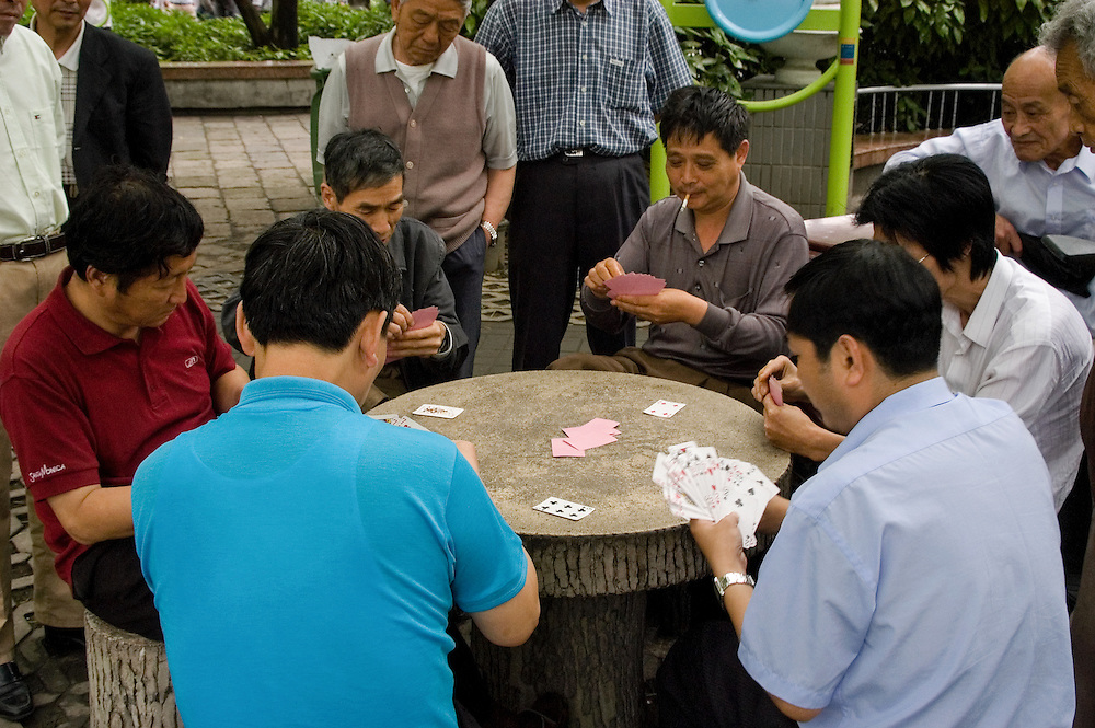 Men gathered around an intense game of cards in a Shanghai park.