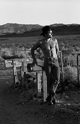 Shirtless man in jeans leaning aganist a mailbox in the desert