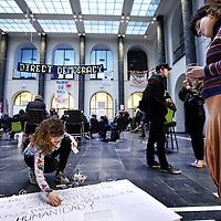Nederland, Amsterdam , 10 maart 2015.<br /> Bezetting van het Maagdenhuis.<br /> Het bestuur van de UvA stuurt niet langer aan op ontruiming van het door studenten bezette Maagdenhuis. Daarmee lijkt de angel uit het verzet te zijn getrokken.<br /> Van een ontruiming van het Maagdenhuis is op korte termijn geen sprake. &lsquo;We merken dat er vruchtbare discussies plaatsvinden en dat er inspirerende bijeenkomsten worden georganiseerd,&rsquo; aldus Yasha Lange, woordvoerder van de UvA. &lsquo;Als plaats voor debat gaat het goed, maar we hebben wel zorgen over het beheer en de veiligheid.<br /> De roep om het aftreden van het College van Bestuur (CvB), die op de avond van de bezetting vorige week woensdag nog zo luid en massaal klonk, hoor je nauwelijks meer. Sterker nog, voorzitter Gunning loopt inmiddels rond in het Maagdenhuis alsof ze onderdeel uitmaakt van de actie.<br /> Onderwijl houden de bezetters zich bezig met vergaderingen, veelal in het Engels vanwege de deelname van een handjevol internationale studenten, lezingen, de opvang van verdwaalde politici en af en toe wat spontane muzikale gastoptredens. De studenten hebben woensdag tot nationale actiedag uitgeroepen. Het is de bedoeling dat op die dag op zoveel mogelijk universiteiten wordt geprotesteerd voor meer democratie en inspraak van studenten op hun eigen hogescholen.<br /> Foto:Jean-Pierre Jans