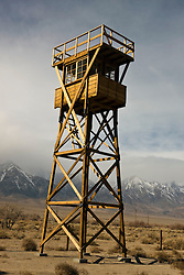 Guard tower number 8 surrounded by barbed wire with snow capped Sierra Nevada mountains in the background, Manzanar National Historic Site, Independence, California