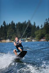 United States, Washington, Lake Sawyer, teen boy wakeboarding.  MR