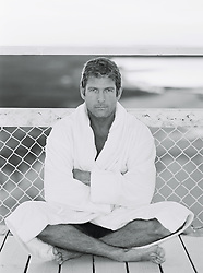 man wearing bathrobe sitting with cross legged by a chain link fence