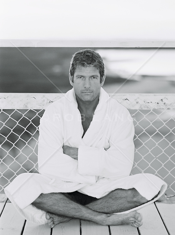 man wearing bathrobe sitting with cross legged by a chain link fence