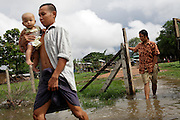 A Burmese family cross a flooded road in Myawaddy, Myanmar.
