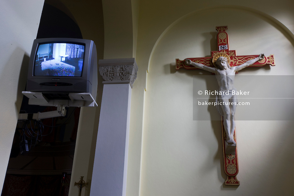 Jesus on the cross and TV coverage of altar inside at St. Lawrence's Catholic church in Feltham, London.