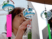 A woman looks at  Edo furin glass wind chimes, at a main junction in the Ginza district of Tokyo, Japan. The traditional chimes, which were until not long ago carried around town by sellers on bamboo poles, date back more than 200 years in Japan. Today there are but a handful of makers left in Japan, with cheaper imports from Korea and China gaining the lion's share of the business for these popular summer decorations. Shinohara' Furinhonpo has been in operation for over 100 years. The family-run business makes around 200,000 of the chimes a year.