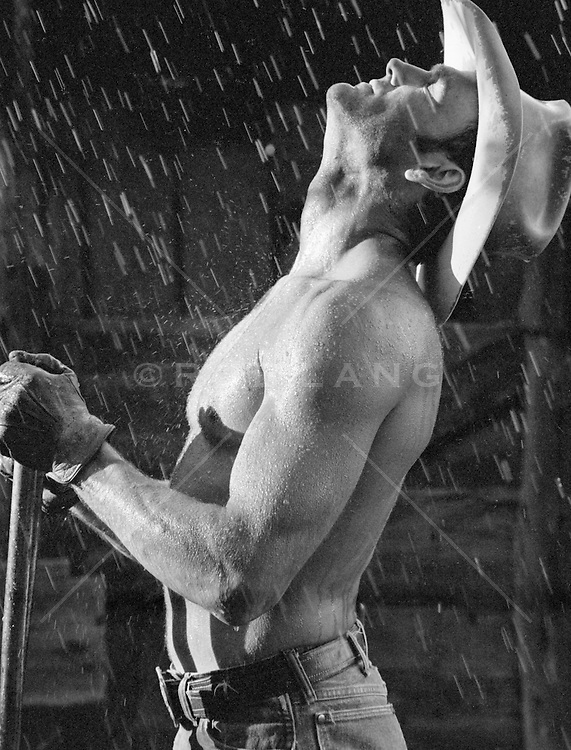 cowboy enjoying the rain on his shirtless body