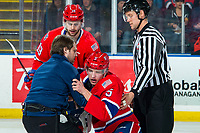 KELOWNA, BC - JANUARY 31: Michael King #19 helps Jordan Chudley #5 of the Spokane Chiefs up off the ice with the assistance of athletic therapist Joe Hurley and linesman Dustin Minty after a fight with Tyson Feist #25 of the Kelowna Rockets during first period at Prospera Place on January 31, 2020 in Kelowna, Canada. (Photo by Marissa Baecker/Shoot the Breeze)