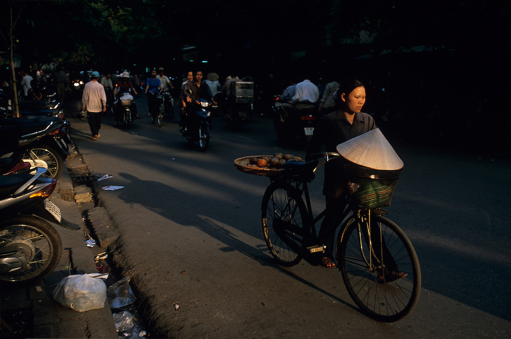 Asia, Vietnam, Hanoi, Woman pushes bicycle through streets in city's Old Quarter at sunset