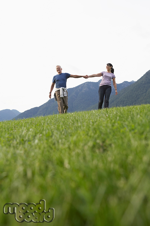 Couple holding hands grass in foreground