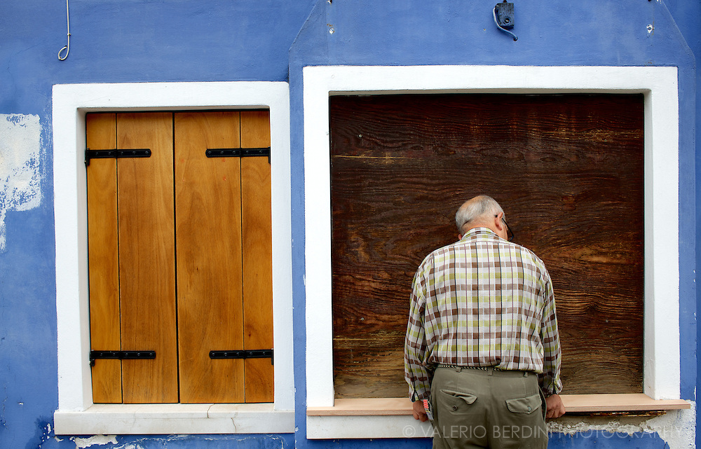 A carpenter replaces a window sill. The Island of Burano, part of the Venetian lagoon in the North East of Italy is famous for its bright painted houses that are constantly kept in shiny conditions by the residents. Empty houses and houses on sale are often in decay.