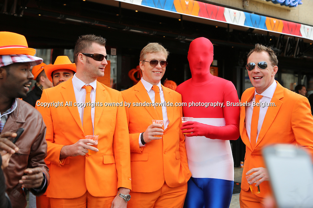 30th April 2013 Amsterdam, Netherlands. Queen Beatrix' abdication day, where her son Prince Willem-Alexander became King of the Netherlands. men in orange suits and a man in a very tight suit in red white and blue drinking beer at the dam square