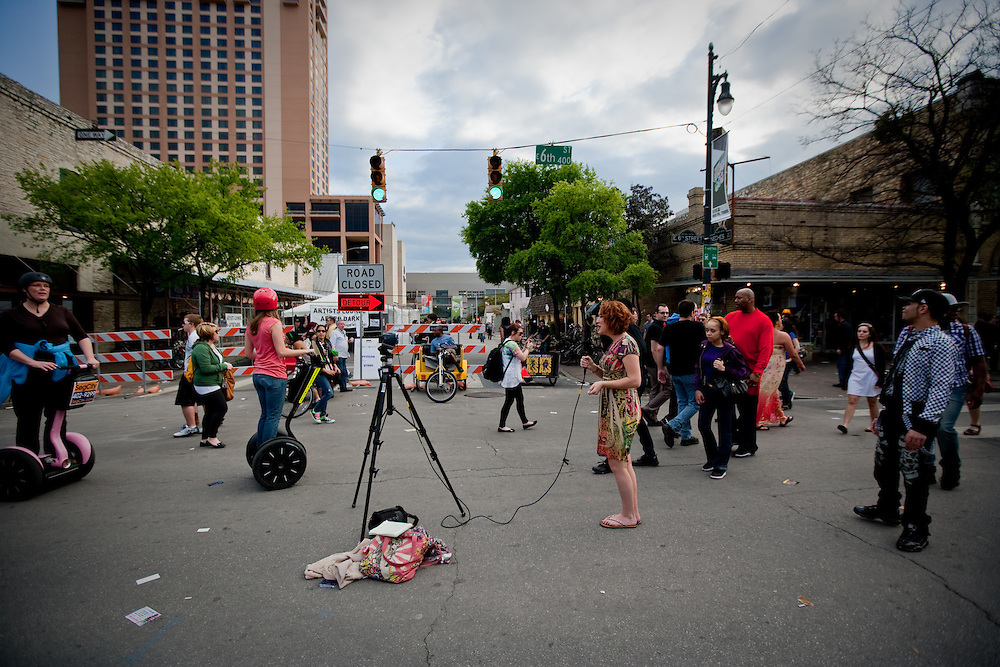 A woman films herself in the middle of 6th street.