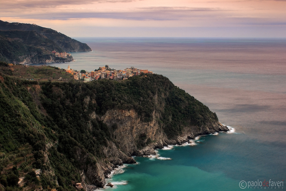 Corniglia and Manarola at sunset, as seen from the Cinque Terre trail, a path that links together the five villages of Cinque Terre in Liguria, Italy..The Cinque Terre are, from east to west, Riomaggiore, Manarola, Corniglia, Vernazza and Monterosso. Corniglia is, among the five village, the only one that has not direct access to the sea..This picture was taken on cold evening of last January, while the sea was calming down after a strong windstorm.