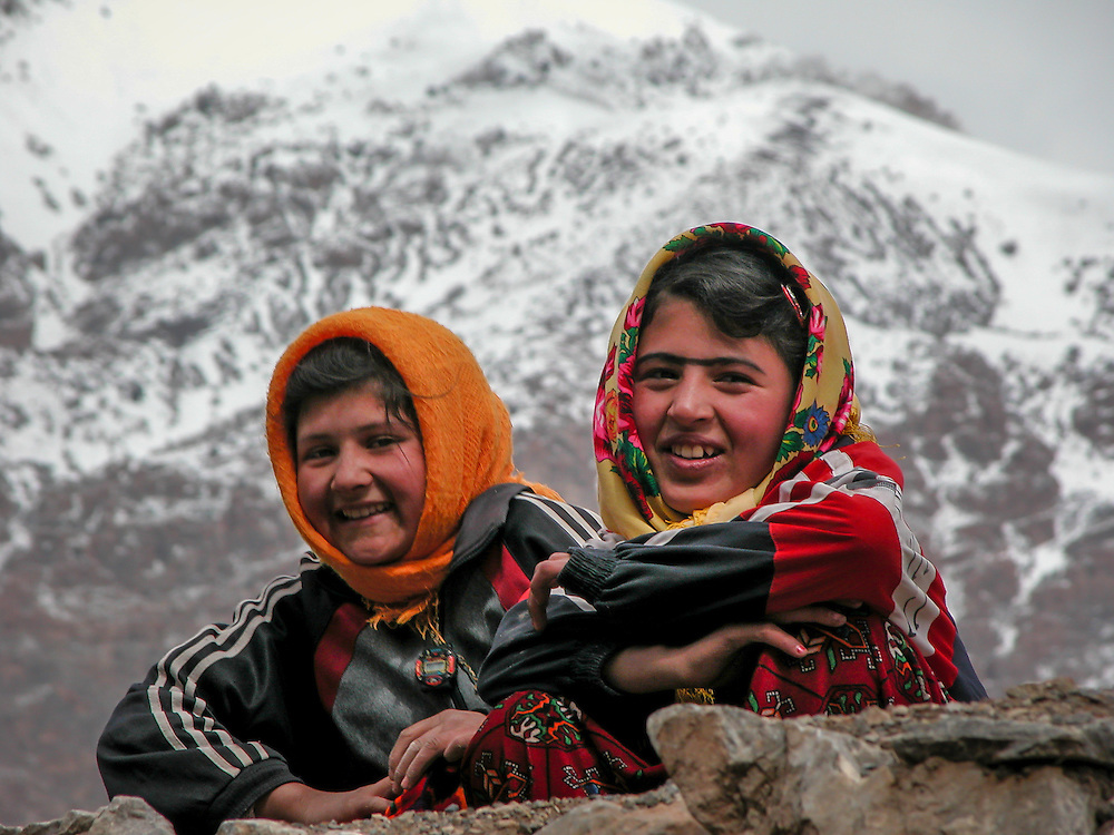 Portrait of two happy Tajik girls inquisitively watching the photographer