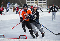 Sled Kid Russell Romeo tries to edge out the Sudbury Bulldog at the goal during Shinny +35 action on the ice Friday morning during the New England Pond Hockey Classic.  (Karen Bobotas/for the Laconia Daily Sun)
