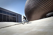 A boy rides a bike near the newly constructed Ordos Museum, which was designed by Chinese architect Ma Yansong. The museum is located in the new city centre of the new town. Driven by a booming economy, the Municipal Government was determined to create this new city, dozens of kilometers away from the current city, on a site that until recently was nothing but the Gobi Desert.