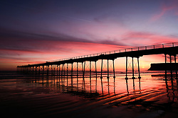 © Licensed to London News Pictures. <br /> 26/03/20167. <br /> Saltburn by the Sea, UK.  <br /> <br /> A spectacular sunrise starts the day over the beach and pier in Saltburn by the Sea.<br /> <br /> Photo credit: Ian Forsyth/LNP